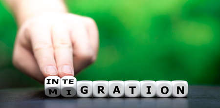 """Hand turns dice and changes the word """"migration"""" to """"integration""""."""