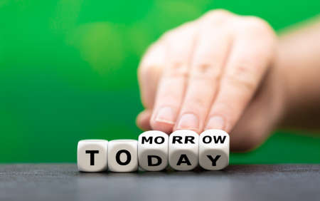"""Hand turns dice and changes the word """"today"""" to """"tomorrow""""."""