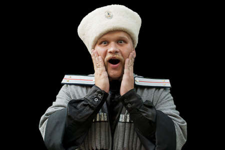 Surprised young man in a cossack clothes on a black background Stock Photo