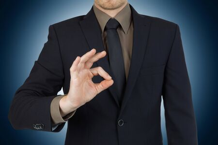 okay: Young successful businessman showing okay symbol