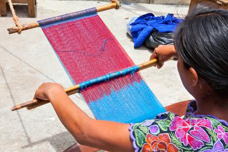 indigenous: Indigenous Tzotzil women weaving a traditional huipil at the loom