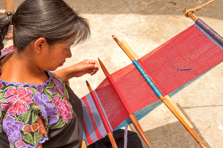 Indigenous Tzotzil woman weaving a traditional huipil at the loom Editorial