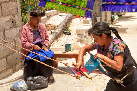 loom: Indigenous Tzotzil women weaving a traditional huipil at the loom