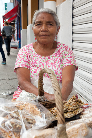 Elderly woman selling traditional Mexican sweets on the street in Oaxaca, Mexico