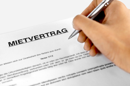 Rental agreement form with signing hand - Concept with the German word lease
