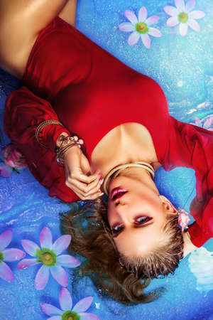 swimsuite: Fashion photo of beautiful young woman with blond hair in red swimsuite relaxing the in water with flowers Stock Photo