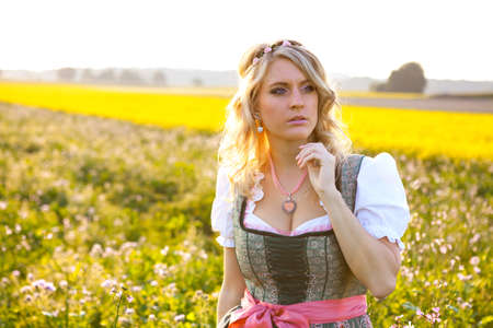 Pretty young german oktoberfest blonde woman wearing a dirndl in yellow flowers field