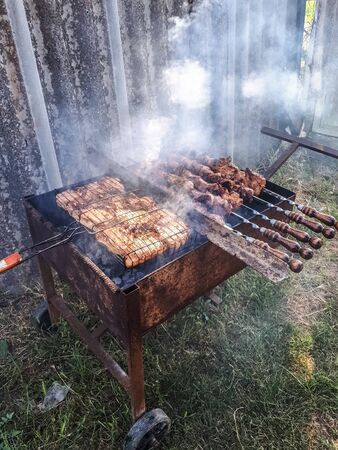Steel barbecue trolley. convenient barbecue. frying meat on the grill. 写真素材