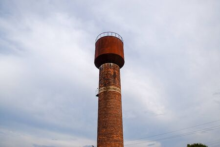Rusty water tower against the sky. Old water pump.