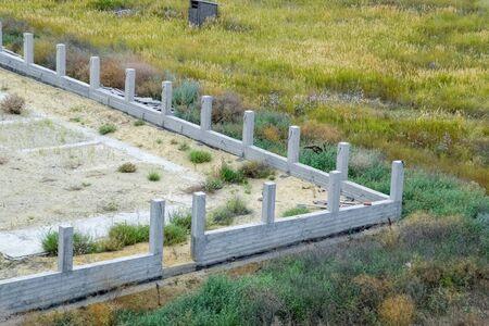 Concrete foundation of the future fence. Concrete fence, fence construction. Reklamní fotografie