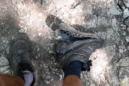 The detached sole on the tourist's sneakers. They broke their boots in the woods.