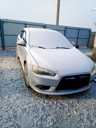 Snow covered car. Morning snow in the yard by car.