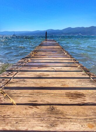Wooden pier by the sea. Boards of the pier and sea waves.