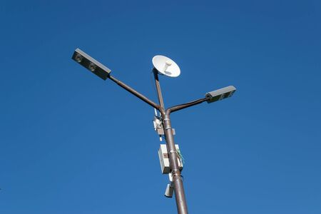 Lamppost with an antenna mounted on it. Pillar against the blue sky. Stock fotó