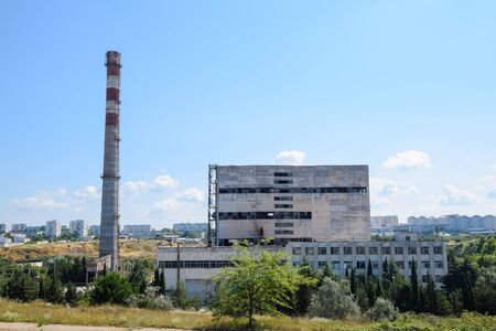 An old Soviet factory with a pipe. Abandoned Soviet industry.