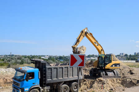 Taman, Russia - July 9, 2019: Excavator on the construction of the road. Heavy machinery for construction. Editöryel