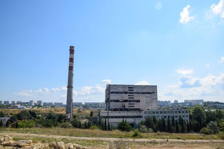 An old Soviet factory with a pipe. Abandoned Soviet industry. Archivio Fotografico