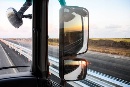 In the cockpit of a truck at dawn. Large rear-view mirrors