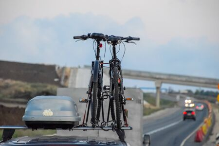 The bikes attached to the roof of the car. Travelling with bikes by car.