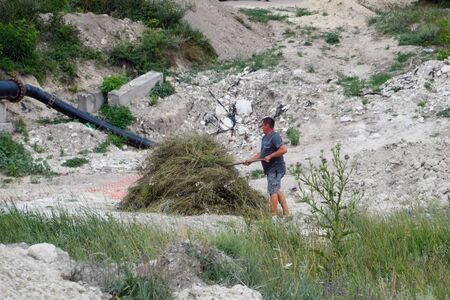 A man folds hay into a skirt. A hay cop. Hay harvesting.
