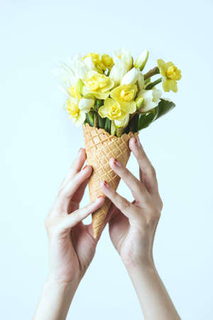 Woman's hand holding a waffle cone with spring yellow flowers bouquet on the mint background. Flat lay, top view. Mothers day, anniversary, greetings.