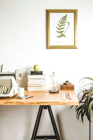 Concept of inspirational home office interior with wooden desk and vintage typewriter. Composition of books, laptop, vintage illustrations of plants, lamp, forest in the jar and office accessories.