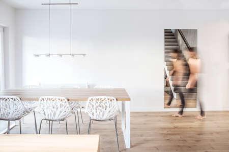Salle à manger scandinave élégante et moderne avec table en bois, chaises design et lampe. Bel espace aux murs blancs.
