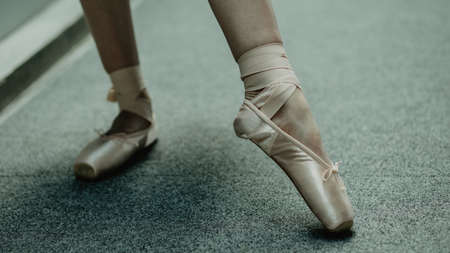 Close up of practice makes perfect- ballerina practices on the dancing hall. Image of ballet shoes in the action.