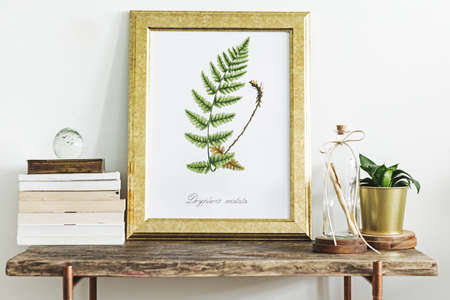 Modern room composition of wooden console with gold mock up poster frame, beautiful plant and letter in bottle. Stylish home interior. Banque d'images