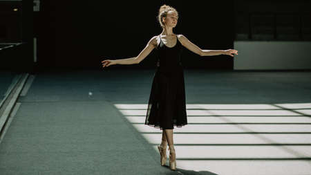 Image of young and slim ballerina practicing ballet position on the dancing hall with geometric window shadows on the floor.