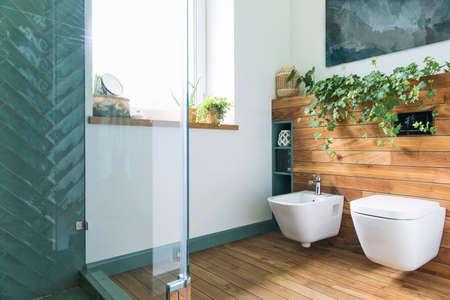 Baño acogedor y de estilo mediterráneo en colores cálidos y madera natural. Foto de archivo