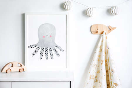 The modern sandinavian newborn baby room with mock up poster frame, wooden car, hanging towel and cotton lamps. Minimalistic and cozy interior with white walls. Archivio Fotografico