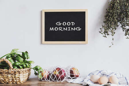 Stylish and coozy interior of kitchen space with small table with mock up frame, herbs, cup of coffee, eggs and vegetables. Vintage concept of kitchen space.. 写真素材