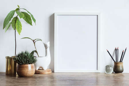 Interior of home space with mock up photo frame, avocado plant , white lama sculpture pot. and office accessories. Vintage concept..