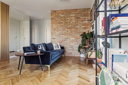 Stylish scandinavian open space with dining and living room with design sofa nad bookstand. Bright and sunny room with plants, poster wall and brown wooden parquet.