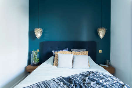 Stylish and modern sunny bedroom interior with small wooden night table , garden in a jar, white bedding, colours pilows and blanket. Space with blue walls and brown wooden parquet. Standard-Bild