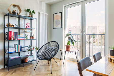 Stylish scandinavian open space with dining and living room with design furniture, bookstand and family table. Bright and sunny room with plants,poster and brown wooden parquet.