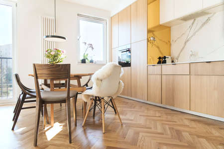 Modern scandinavian open space interior of kitchen and dining room with design furniture, black fridge, marble walls and brown wooden parquet. Wooden and marble walls, elegant accessories. Standard-Bild