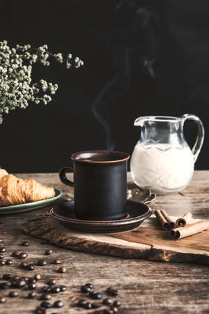 The vintage and stylish composition in kitchen interior with a cup of coffee, milk and croissant. Winter and autumn concept of morning breakfast. Black background.