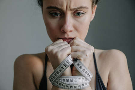 Young woman with anorexia and depression with black suit She is measuring her body. Sadness, nostlagic, depression. disgust for eating. Mental problems of young people. Close up. Portrait. Stock Photo