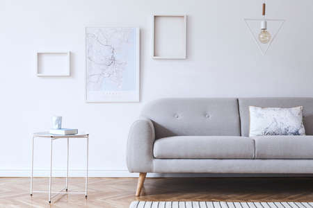 Minimalistic scandinavian white interior with design sofa, poster, coffee table and mock up frames. White background walls and modern triangle lamp.