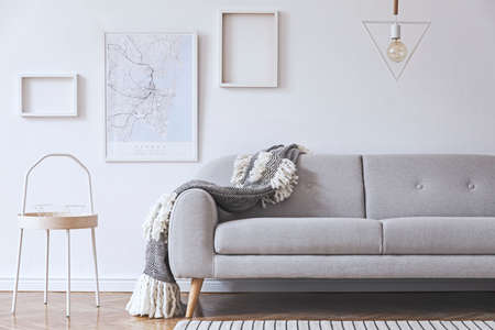 Stylish and cozy scandinavian white interior with design, coffee table, pillows, blanket, gramophone and mock up photo frames. White background walls and modern triangle lamp.