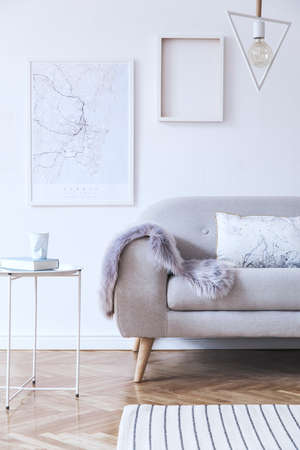 Minimalistic scandinavian white interior with design sofa, poster, coffee table, cozy blanket,and mock up frames. White background walls and modern triangle lamp. Zdjęcie Seryjne