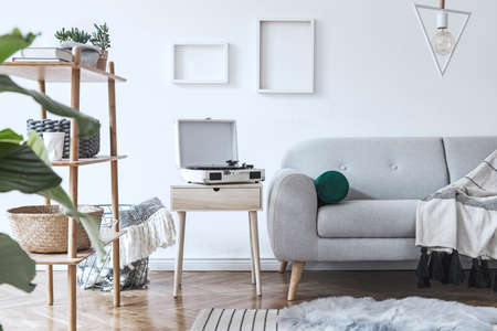 Stylish and cozy scandinavian white interior with design sofa, bookstand with accessories, pillows, blanket, gramophone and mock up photo frames. White background walls and modern triangle lamp.