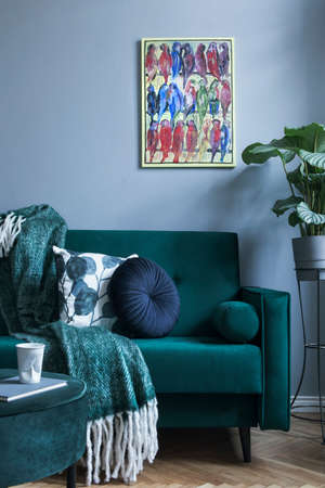 Grey luxury interior with green velvet sofa, pillows, pouf, blanket and tropical plant. Modern composition with mockup image. Brown wooden parquet.