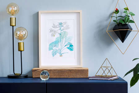 Interior floral poster mock up with vertical wooden frame, table lamp, gold pyramid, accessories and hanging plants in geometric pot on the grey wall background. Concept with navy blue shelf.