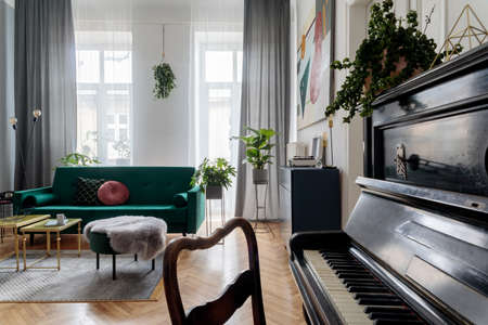 Bright and sunny luxury home interior with design green velvet sofa, armchair, table, commode, pouf and accessroies. Big windows. A lot of plants. Stylish decor of living room. View from the piano. Stockfoto