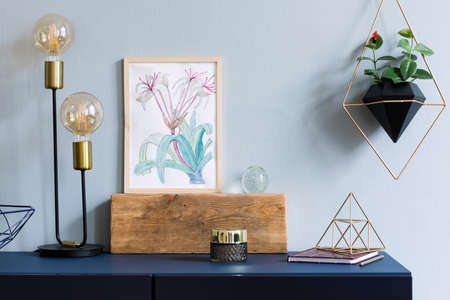 Home interior with poster mock up with wooden frame, table lamp, gold pyramid, accessories and hanging plants in geometric pot on the grey wall background. Minimal concept of navy blue shelf. Stock Photo