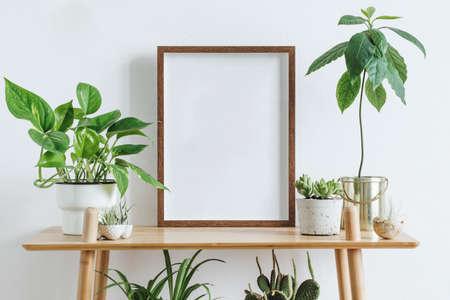 Intérieur de la chambre scandinave avec cadre photo maquette sur l'étagère en bambou marron avec de belles plantes dans différents pots hipster et design. Murs blancs. Concept d'étagères moderne et floral.