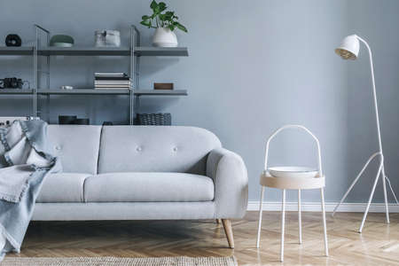Stylish nordic living room with design sofa with elegant blanket, coffee table,white lamp, plants and bookstand on the grey wall. Brown wooden parquet. Concept of minimalistic interior.